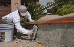 stucco repair man repairing stucco
